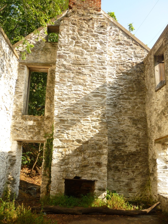 Looking to the right side of the house (when facing it), where a stone chimney and two doors remain.